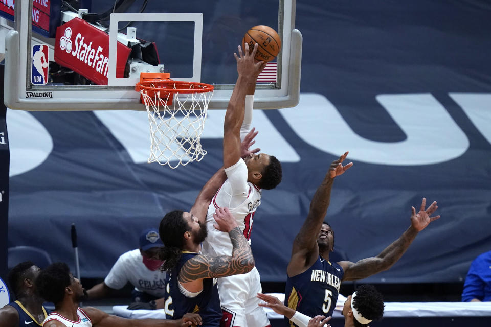 Chicago Bulls center Daniel Gafford goes to the basket between New Orleans Pelicans guard Eric Bledsoe (5) and center Steven Adams during the first half of an NBA basketball game in New Orleans, Wednesday, March 3, 2021. (AP Photo/Gerald Herbert)