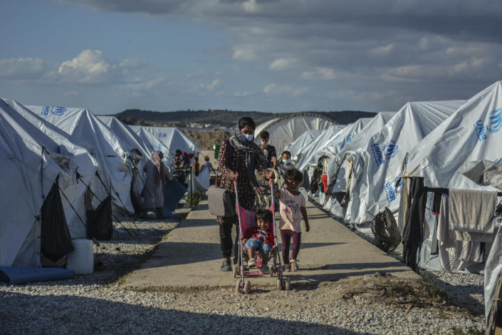 FILE - In this Wednesday, Oct. 14, 2020 file photo, Migrants walk after a rainstorm at the Kara Tepe refugee camp, on the northeastern Aegean island of Lesbos, Greece, Wednesday, Oct. 14, 2020. Greece's notoriously squalid refugee camp of Moria burnt down last September on the island of Lesbos. It left around 12,000 people in need of emergency housing as winter approached. European leaders then vowed such squalid facilities would be a thing of the past. But aid agencies say that a year later the conditions for asylum seekers on the eastern Greek islands have barely improved. (AP Photo/Panagiotis Balaskas, File)