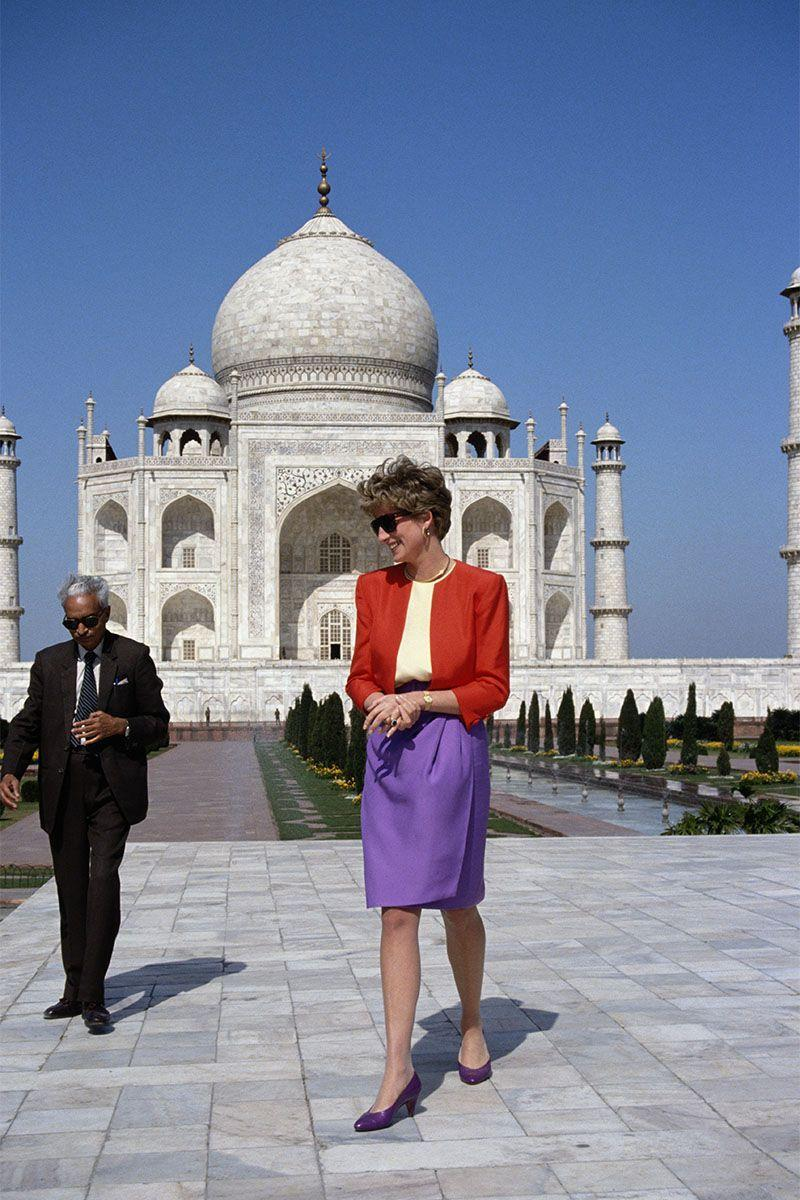 <p>In a red jacket, creme-colored top and purple skirt and shoes outside the Taj Mahal. </p>