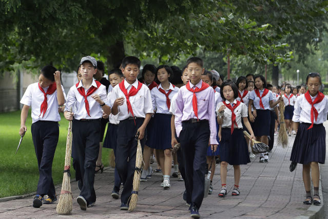 <p>Schoolchildren carry brooms as they walk to various public spaces to sweep and weed the grass in efforts to keep the city clean on July 28, 2017, in Pyongyang, North Korea. (Photo: Wong Maye-E/AP) </p>