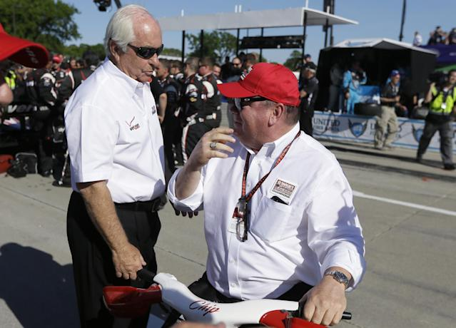 Roger Penske, left, talks with Chip Ganassi after the first of two auto races at the IndyCar Detroit Grand Prix, Saturday, May 31, 2014, on Belle Isle in Detroit. Penske driver Will Power finished 0.3308 seconds ahead of Graham Rahal in the race. (AP Photo/Carlos Osorio)