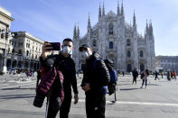 People wearing sanitary masks take a selfie in front of the Duomo gothic cathedral, in Milan, Italy, Monday, Feb. 24, 2020. At least 190 people in Italy's north have tested positive for the COVID-19 virus and four people have died, including an 84-year-old man who died overnight in Bergamo, the Lombardy regional government reported. (Claudio Furlan/Lapresse via AP)
