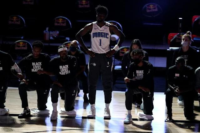 NBA player Jonathan Isaac stands as teammates kneel during the national anthem ahead of Orlando's game with Brooklyn on Friday (AFP Photo/POOL)
