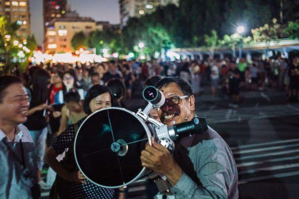 PHOTO: People set up telescopes to witness a rare lunar eclipse, July 27, 2018 in Taipei, Taiwan. (Billy H.C. Kwok/Getty Images)