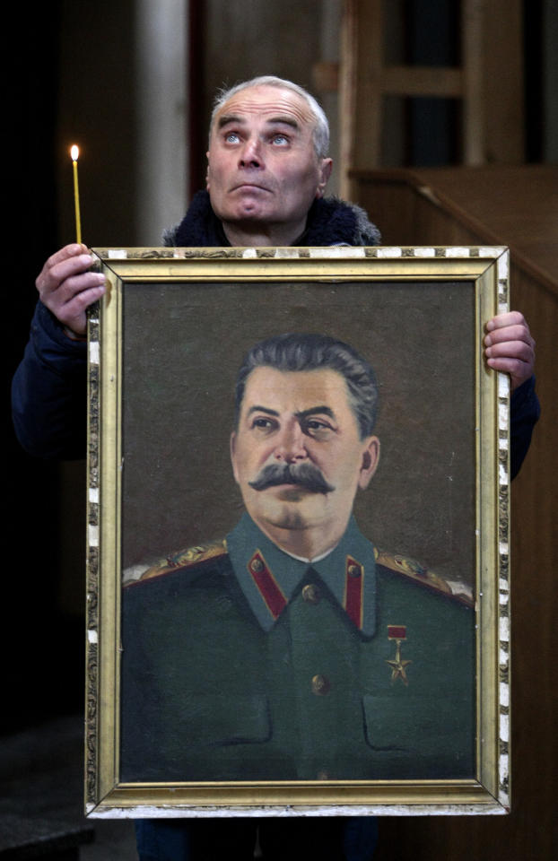 A Georgian holds a portrait of former Soviet dictator Joseph Stalin and a candle marking the 60th anniversary of his death as he stands in a church in Stalin's home town of Gori, some 80 km (50 miles) west of the Georgian capital Tbilisi, Tuesday, March 5, 2013. Georgian communists, who flocked to Stalin's hometown of Gori for the anniversary on Tuesday, hope that the government of Prime Minister Bidzina Ivanishvili, whose bloc defeated Saakashvili's party in parliamentary elections last fall, will restore the Stalin monument torn down on Georgian President Mikhail Saakashvili's orders. (AP Photo/Shakh Aivazov)