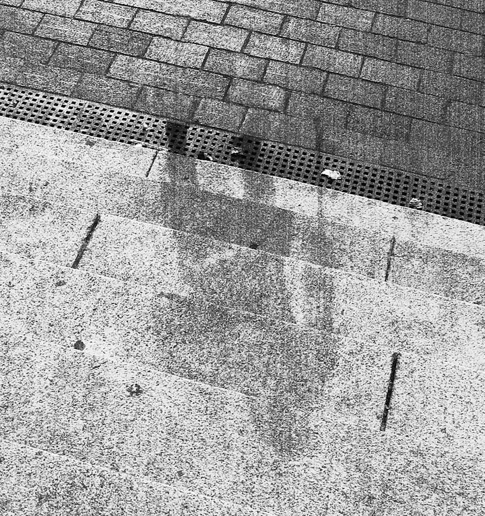 A shadow of a person is marked on stone steps