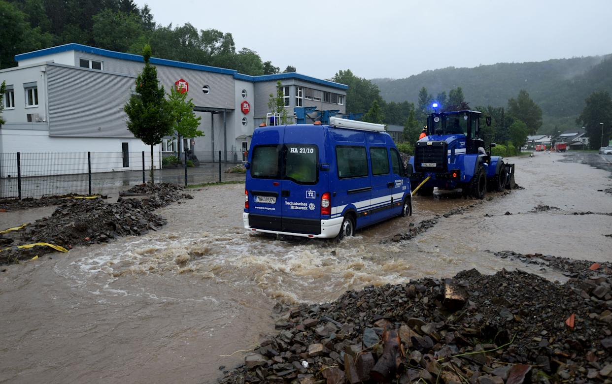 A wheel loader of Germany's technical relief agency THW (Technisches Hilfswerk) pulls a THW van out of the water in a flooded street on July 14, 2021 in Hagen, western Germany, after heavy rain hit parts of the country, causing widespread flooding. (Photo by Ina FASSBENDER / AFP) (Photo by INA FASSBENDER/AFP via Getty Images)