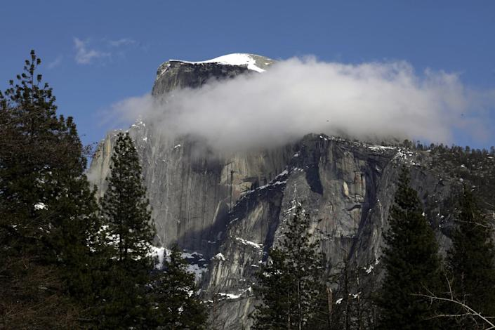 """Yosemite Half Dome dusted with snow and clouds in Yosemite National Park is closed to visitors due to the coronavirus. <span class=""""copyright"""">(Carolyn Cole/Los Angeles Times)</span>"""