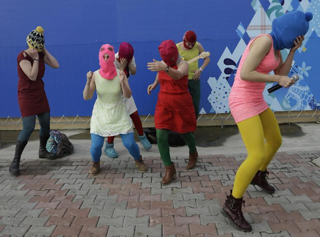 Nadezhda Tolokonnikova covers her face to protect herself from a Cossack militiaman while she and fellow members of the punk group Pussy Riot, including Maria Alekhina, second left, in the pink balaclava, stage a protest performance in Sochi, Russia, on Wednesday, Feb. 19, 2014. The group had gathered in a downtown Sochi restaurant, about 30km (21miles) from where the Winter Olympics are being held. They ran out of the restaurant wearing brightly colored clothes and ski masks and were set upon by about a dozen Cossacks, who are used by police authorities in Russia to patrol the streets. (AP Photo/Morry Gash)