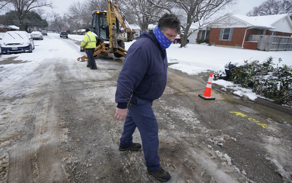 Kevin Young, with the City of Richardson water department, looks at an area where water main pipe failed due to extreme cold in a neighborhood Wednesday, Feb. 17, 2021, in Richardson, Texas. Millions remain without power in the record-breaking cold, mostly in Texas. (AP Photo/LM Otero)