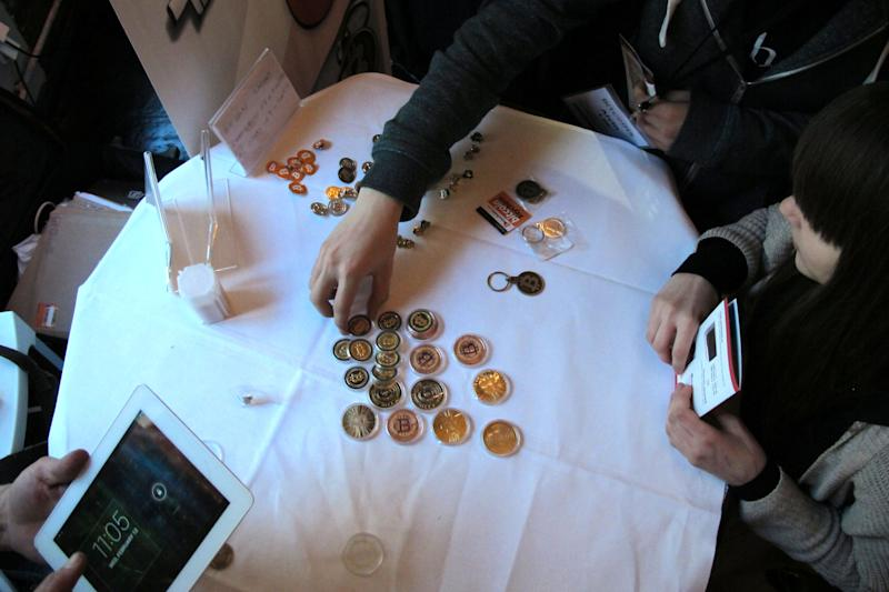 FILE - In this Feb. 12, 2014 file photo, attendees of the Inside Bitcoins conference in Berlin examine Bitcoin buttons. The website of major Bitcoin exchange Mt. Gox is offline amid reports it suffered a debilitating theft of the virtual currency, and the URL of the Tokyo-based outfit returns a blank page on Tuesday, Feb. 25, 2014. (AP Photo/Frank Jordans, File)