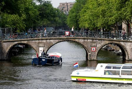 FILE PHOTO: Tourists boats pass on a canal in Amsterdam, Netherlands, May 16, 2018. REUTERS/Francois Lenoir/File Photo