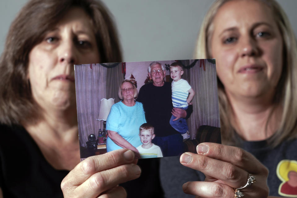 Kelly Brown, right, and Stacy Nash hold up a December 2019 photograph of their parents John and Judy Trzebiatowski, in their home, Friday, June 25, 2021, in Menomonee Falls, Wis. Both parents died from COVID-19. (AP Photo/Morry Gash)