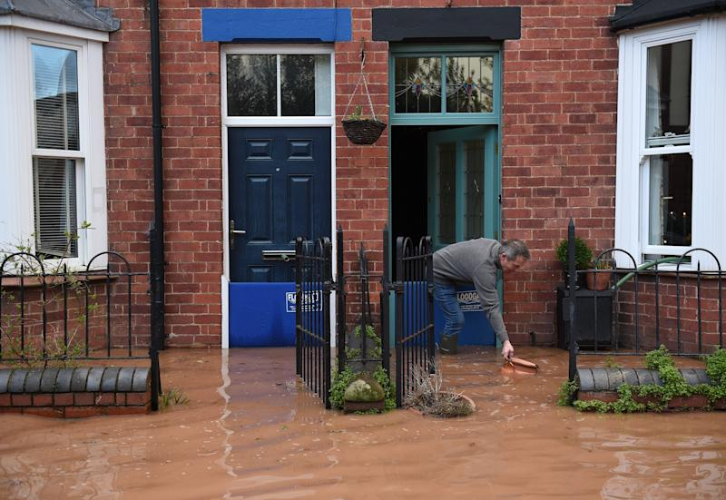 A man rescues a floating plant pot from flood water, outside of a flood-bound house in Tenbury Wells, after the River Teme burst its banks in western England, on February 16, 2020, after Storm Dennis caused flooding across large swathes of Britain. - A man died after falling into a river on Sunday as Storm Dennis swept across Britain with the army drafted in to help deal with heavy flooding and high winds. (Photo by Oli SCARFF / AFP) (Photo by OLI SCARFF/AFP via Getty Images)