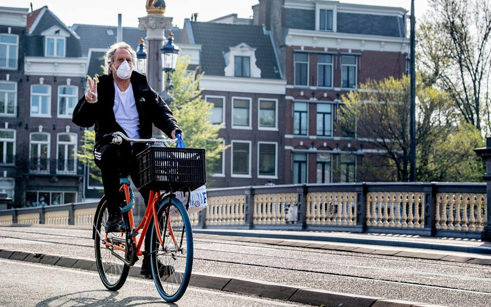 A man rides a bicycle while wearing a face mask in Amsterdam - Robin Utrecht/SOPA Images/LightRocket via Getty Images