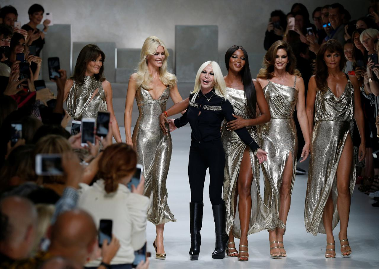 Italian designer Donatella Versace (3L) acknowledges the applause with former top models Carla Bruni (L), Claudia Schiffer, Naomi Campbell, Cindy Crawford and Helena Christensen (R) at the end of Versace Spring/Summer 2018 show at the Milan Fashion Week in Milan, Italy, September 22, 2017. REUTERS/Stefano Rellandini     TPX IMAGES OF THE DAY