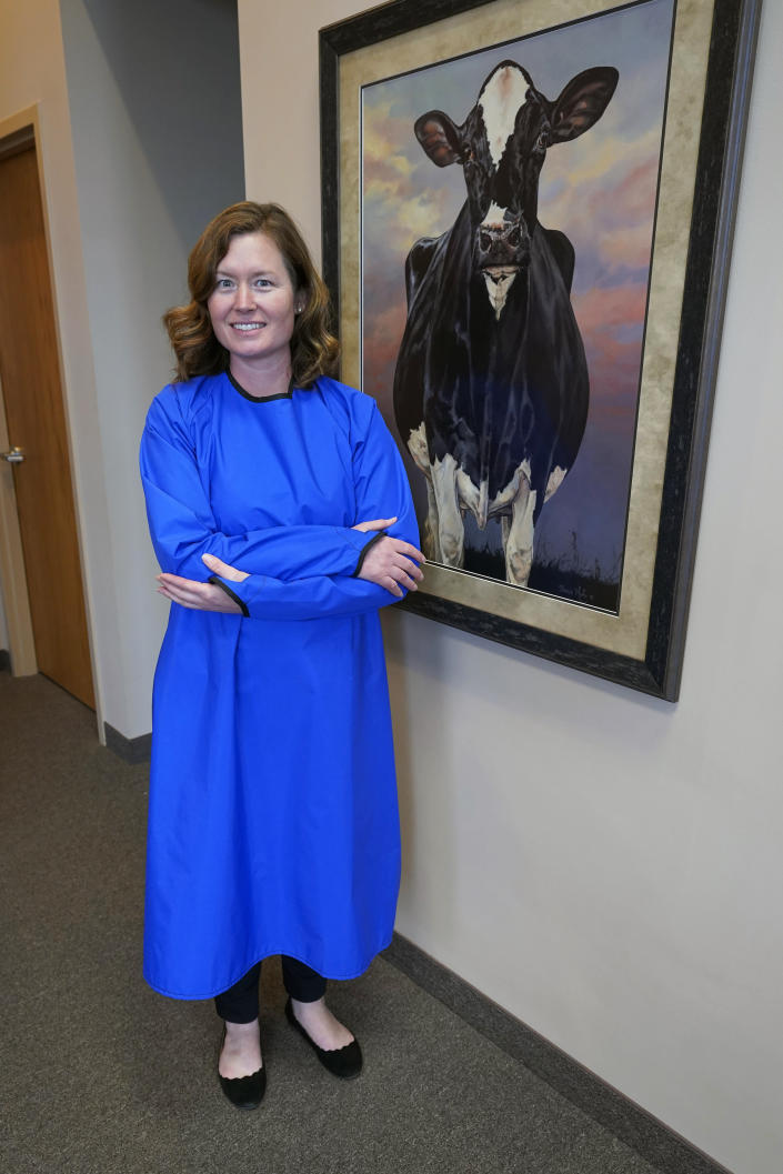 Ann Quigley poses Tuesday, Dec. 15, 2020, in a waterproof gown intended for milking cows made by Udder Tech Inc., a Rosemount, Minnesota-based dairy supply company. Minnesota bought 2,300 waterproof gowns intended for milking cows from Udder Tech Inc. The special gowns cost about $46 each when freight was included. (AP Photo/Jim Mone)