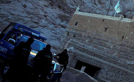 FILE PHOTO - Special police forces stand guard as a Greek monk is seen on the top of a church at Saint Catherine's monastery, in the Sinai Peninsula