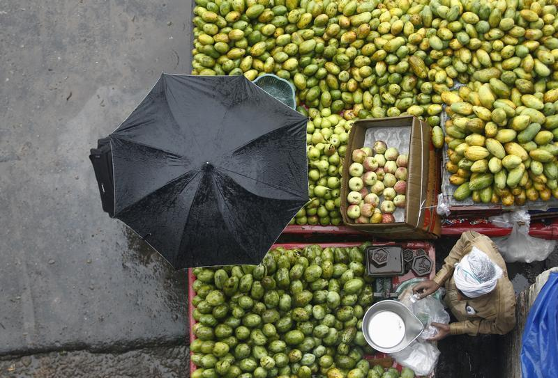 A vendor sells fruits during a heavy monsoon rain shower in New Delhi
