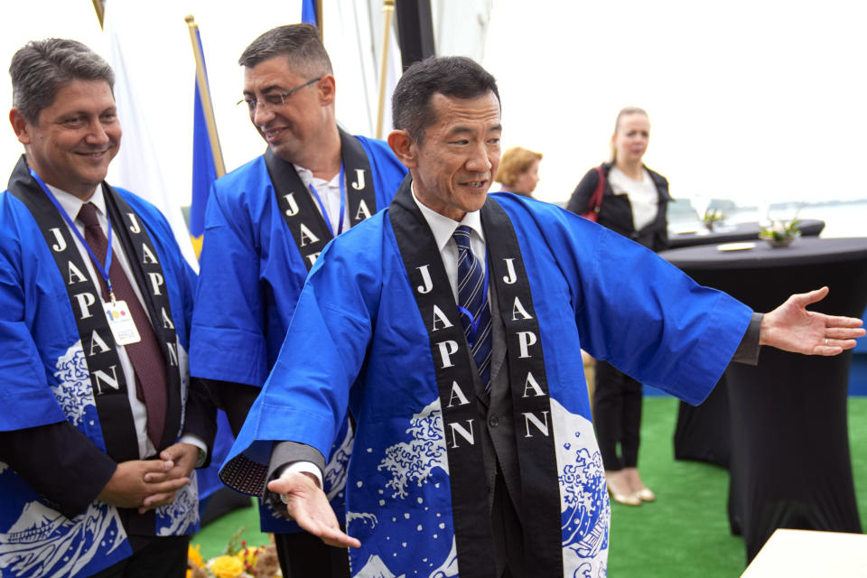 Japanese ambassador to Romania Hiroshi Ueda, right, gestures on the river Danube at the construction site of a suspension bridge in Braila, Romania, Thursday, Aug. 26, 2021. The bridge, built by Japanese and Italian companies, with a span of 1,974.3 meters, will be the largest of its kind in Romania and the third in the European union. The event also marked 100 years of diplomatic relations between Japan and Romania. (AP Photo/Vadim Ghirda)