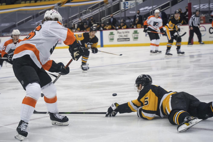 Pittsburgh Penguins' Mike Matheson (5) dives trying to stop a pass to Philadelphia Flyers' Joel Farabee, left, during the second period of an NHL hockey game, Tuesday, March 2, 2021, in Pittsburgh. Farabee got the puck and then scored on the play. (AP Photo/Keith Srakocic)