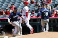 Los Angeles Angels designated hitter Shohei Ohtani, center, beats Seattle Mariners first baseman Ty France, left, to first base on a ground ball single as relief pitcher Anthony Misiewicz, right, is late to cover during the seventh inning of a baseball game in Anaheim, Calif., Sunday, July 18, 2021. (AP Photo/Alex Gallardo)