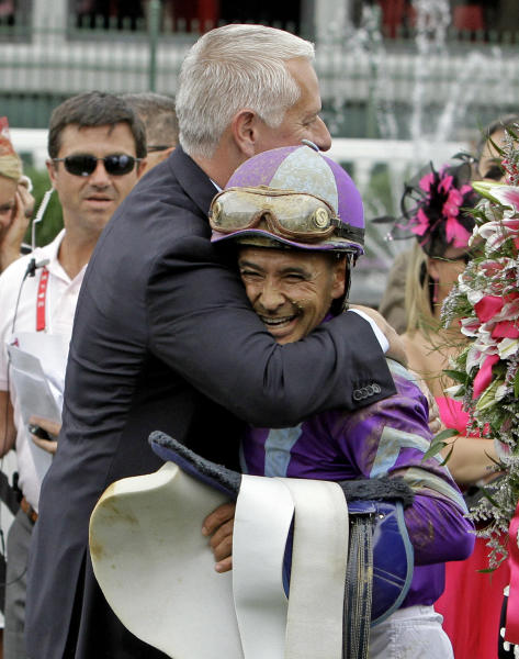 Trainer Todd Pletcher hugs jockey Mike Smith after Smith rode Princess of Sylmar to a win in the 139th Kentucky Oaks at Churchill Downs Friday, May 3, 2013, in Louisville, Ky.(AP Photo/Garry Jones)