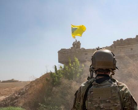 A U.S. soldier oversees members of the Syrian Democratic Forces as they demolish a YPG fortification Syria