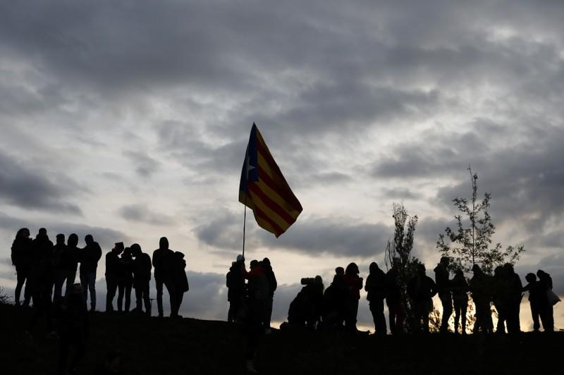 Demonstrators hold an Estelada as members of Catalan protest group Democratic Tsunami block the AP-7 highway in Girona
