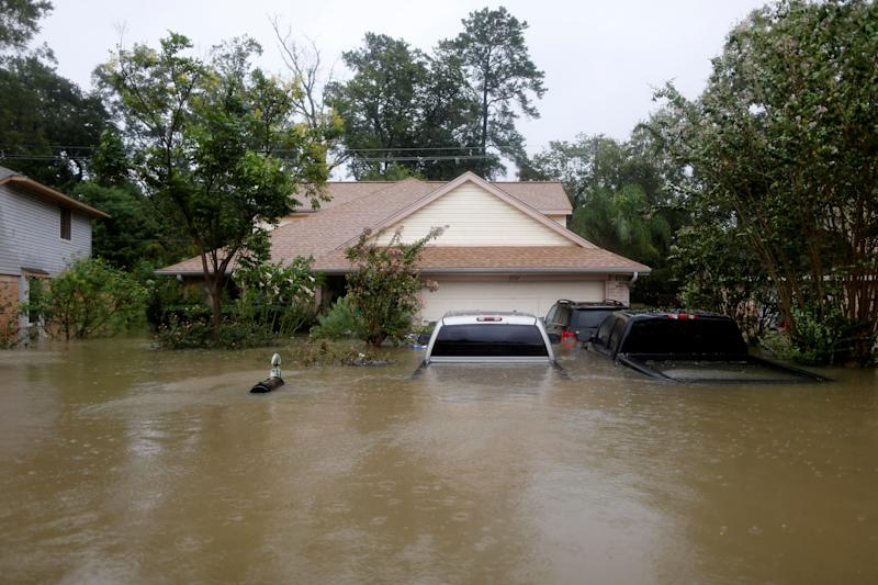 Houses and cars are seen partially submerged by flood waters in east Houston on Monday.  (Jonathan Bachman / Reuters)