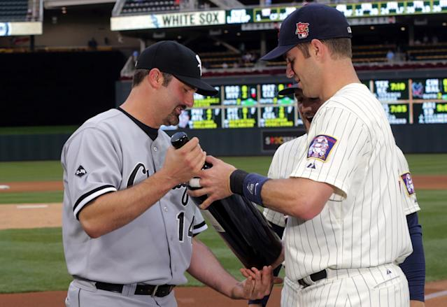 Chicago White Sox's Paul Konerko, left, is presented with a large bottle of wine by Minnnesota Twins' Joe Mauer, right, and Glen Perkins prior to a baseball game, Wednesday, Sept. 3, 2014, in Minneapolis. It was part of honoring Konerko in his farewell baseball season. (AP Photo/Jim Mone)