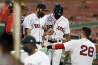 Boston Red Sox infielder Jose Peraza, center left, enters the dug out after being injured while pitching during the ninth inning of a baseball game against the Tampa Bay Rays, Thursday, Aug. 13, 2020, in Boston. (AP Photo/Michael Dwyer)