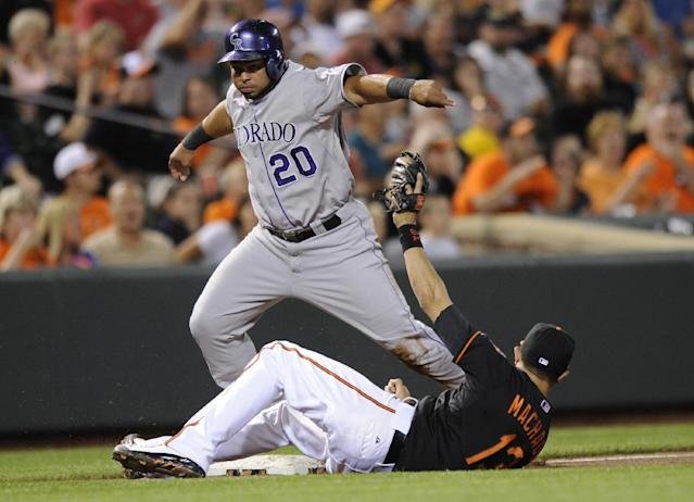 Colorado Rockies' Wilin Rosario (20) is safe at third on a wild pitch against the Baltimore Orioles third baseman Manny Machado (13) during the fifth inning of a baseball game, Friday, Aug. 16, 2013, in Baltimore. (AP Photo/Nick Wass)