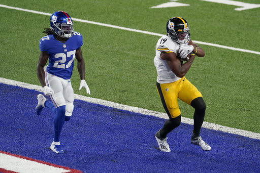 Pittsburgh Steelers wide receiver JuJu Smith-Schuster (19) comes down with a touchdown pass in front of New York Giants cornerback Isaac Yiadom (27) during the second quarter of an NFL football game Monday, Sept. 14, 2020, in East Rutherford, N.J. (AP Photo/Frank Franklin II)