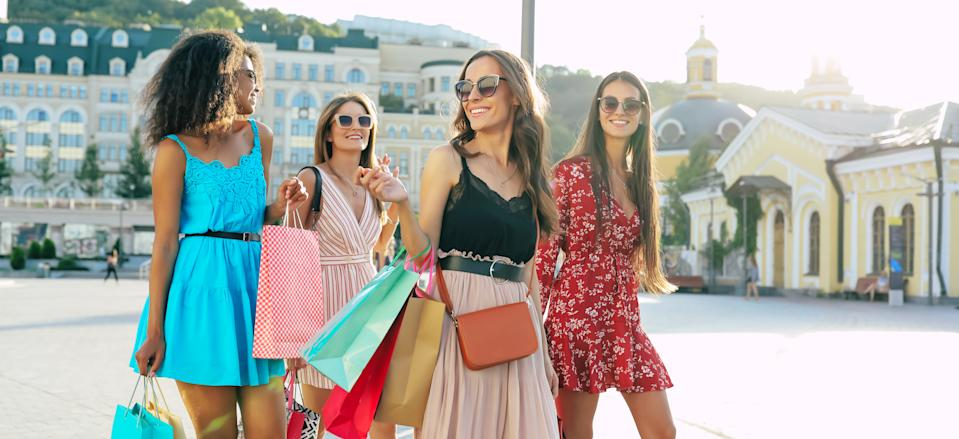 Close-up photo of young wonderful girls walking in the city center after shopping, talking to each other, smiling and posing in multicolored dresses.