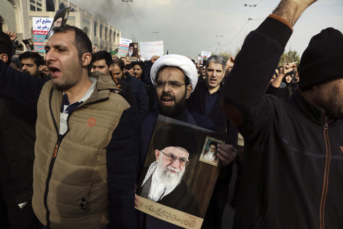"""A cleric holds a poster of Iranian Supreme Leader Ayatollah Ali Khamenei and late revolutionary founder Ayatollah Khomeini, top right, while chanting slogans in a demonstration over the U.S. airstrike in Iraq that killed Iranian Revolutionary Guard Gen. Qassem Soleimani in Tehran, Iran, Jan. 3, 2020. Iran has vowed """"harsh retaliation"""" for the U.S. airstrike near Baghdad's airport that killed Tehran's top general and the architect of its interventions across the Middle East, as tensions soared in the wake of the targeted killing. (AP Photo/Vahid Salemi)"""
