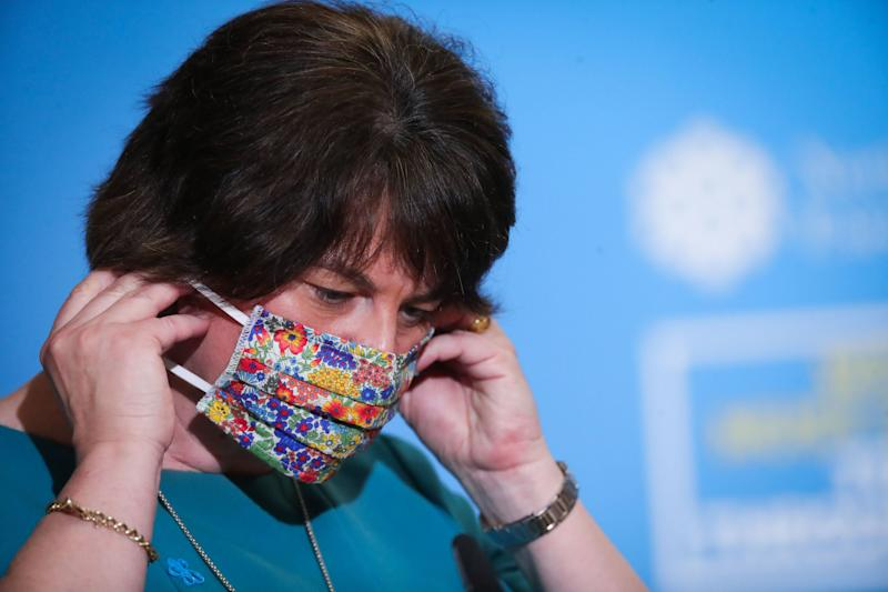 Northern Ireland first minister Arlene Foster removes her face covering before announcing new restrictions (PA)