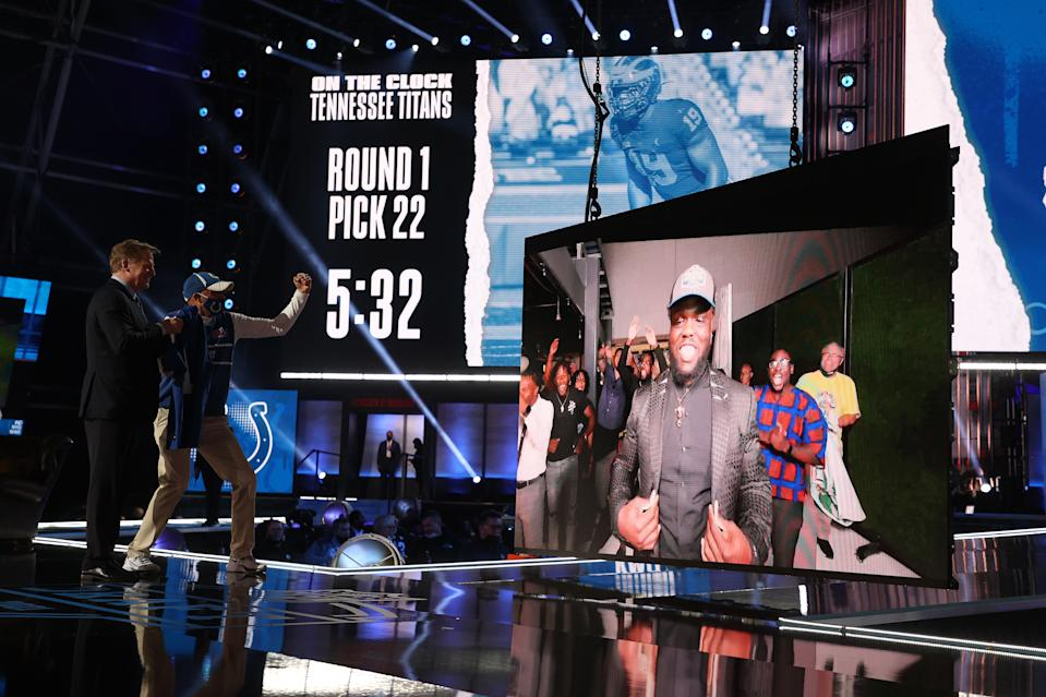 Kwity Paye is shown on a screen after being announced as the 21st draft pick with Roger Goodell and a Colts fan on stage in Cleveland looking at the screen.