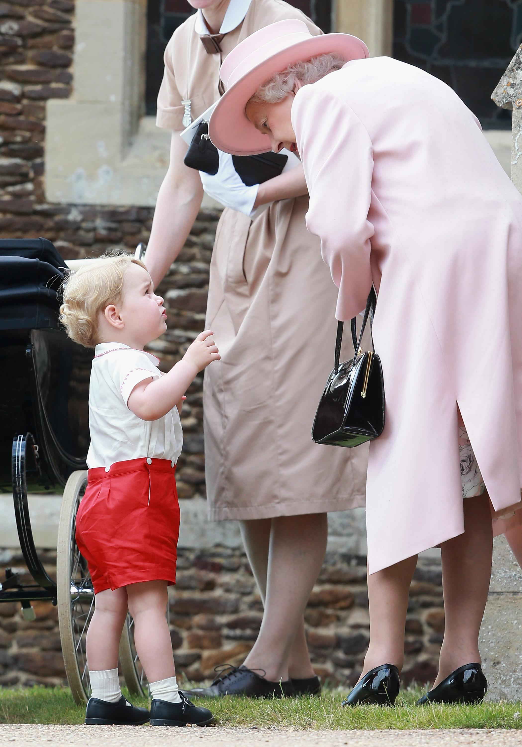 The Queen bends down to talk to Prince George at Princess Charlotte's christening