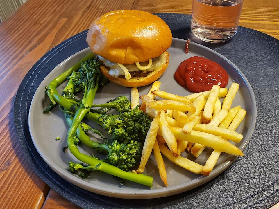 plate with burger, broccolini, french fries, and ketchup