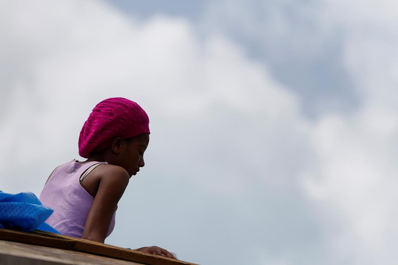 <p>Che Niesha,16, from Barbuda, sits on the roof of a home at Codrington on the island of Barbuda just after a month after Hurricane Irma struck the Caribbean islands of Antigua and Barbuda, October 7, 2017. REUTERS/Shannon Stapleton </p>