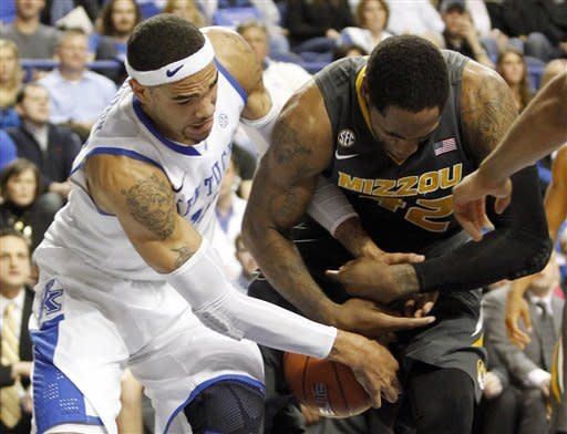 CORRECTS DAY OF WEEK - Kentucky's Willie Cauley-Stein, left, and Missouri's Alex Oriakhi battle for a loose ball during the first half of an NCAA college basketball game at Rupp Arena in Lexington, Ky., Saturday, Feb. 23, 2013. (AP Photo/James Crisp)