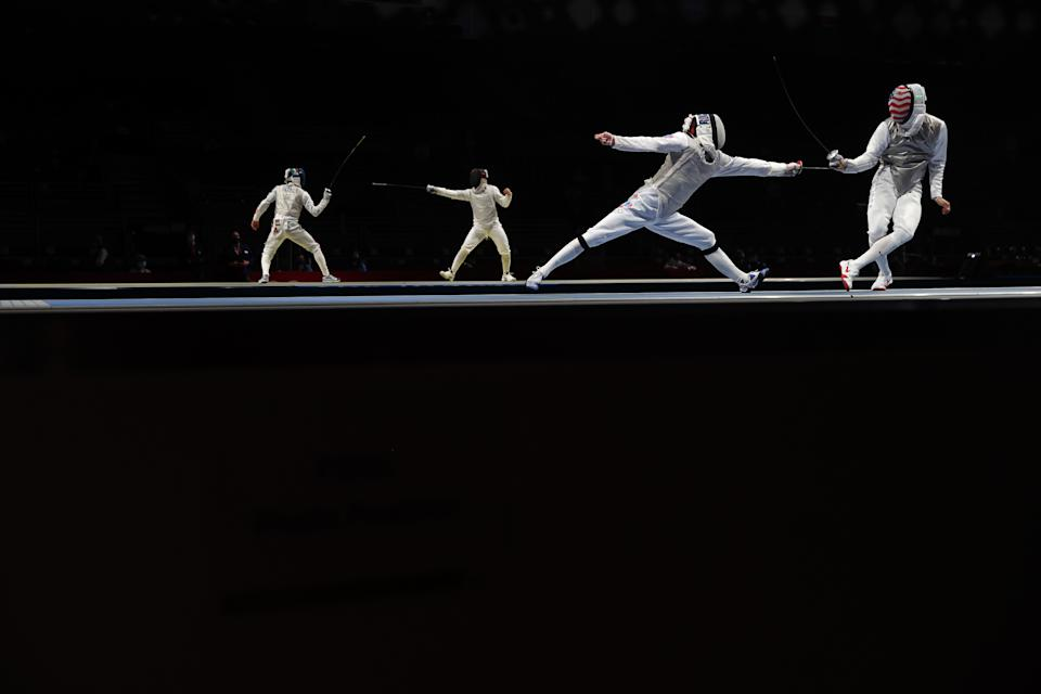 <p>Vladislav Mylnikov of Team ROC and Gerek Meinhardt of Team United States compete in the foreground as Daniele Garozzo of Team Italy and Mohmed Hassan of Team Egypt compete in the background in Men's Foil Individual second round on day three of the Tokyo 2020 Olympic Games at Makuhari Messe on July 26, 2021 in Chiba, Japan. (Photo by Julian Finney/Getty Images)</p>