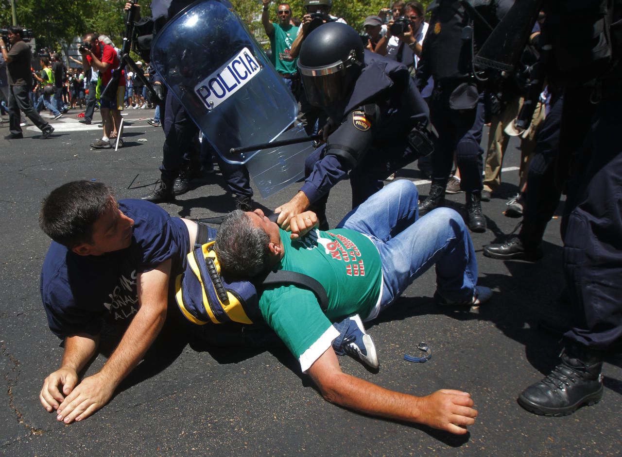 Demonstrators clash with riot police during the coal miner's march to the Minister of Industry's building in Madrid, Wednesday, July 11, 2012. The miners' march into the capital was the culmination for some of a nearly three-week trek from the regions where they eke out a living. Miners who walked 18 days from northern and eastern mining regions were received as heroes on Tuesday night as they entered the Puerta del Sol, one of the city's main plazas. (AP Photo/Andres Kudacki)