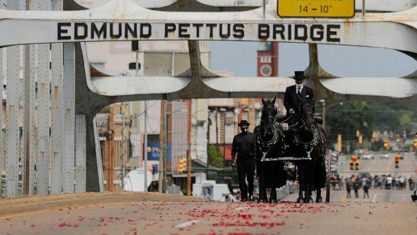 PHOTO: The casket of Rep. John Lewis moves over the Edmund Pettus Bridge by horse-drawn carriage during a memorial service for Lewis, July 26, 2020, in Selma, Ala. (Brynn Anderson/AP)