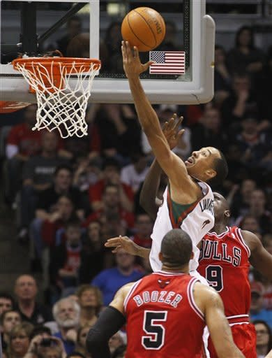 Milwaukee Bucks' Shaun Livingston, center, puts up a shot against Chicago Bulls' Carlos Boozer (5) and Luol Deng (9) during the first half of an NBA basketball game Saturday, Feb. 4, 2012, in Milwaukee. (AP Photo/Jeffrey Phelps)