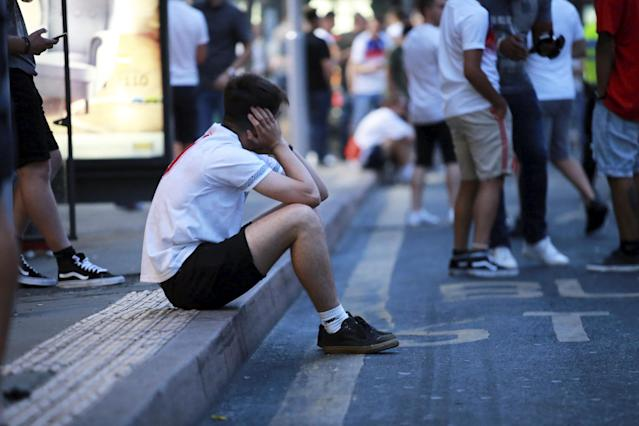 <p>A lone England fan sits on the pavement in Nottingham as the disappointing result sinks in. (SWNS) </p>
