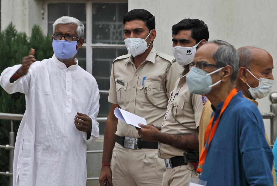 Members of the festival organizing team at the Kali Bari Hindu temple explain to policemen precautions they have taken for Durga Puja celebrations in New Delhi, India, Thursday, Oct. 22, 2020. Most of the festival festivities are being scaled down following the health officials warning about the potential for the coronavirus to spread during the religious festival season, which is marked by huge gatherings in temples and shopping districts. (AP Photo/Manish Swarup)