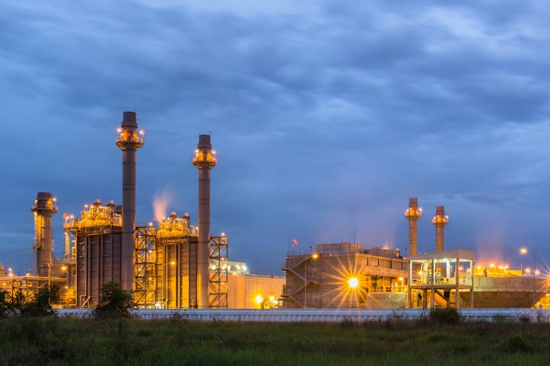 A gas-powered power plant lit up at night.