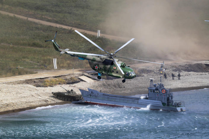 """A Russian navy landing vessel unloads an armored vehicle as a military helicopter flies overhead during Russian military maneuvers Vostok 2018 on the training ground """"Klerk"""", about 50 kilometers (31 miles) south of Vladivostok, Russian Far East port, Russia, Saturday, Sept. 15, 2018. The weeklong Vostok 2018 maneuvers are the largest war games Russia ever had. (AP Photo/Sergei Grits)"""
